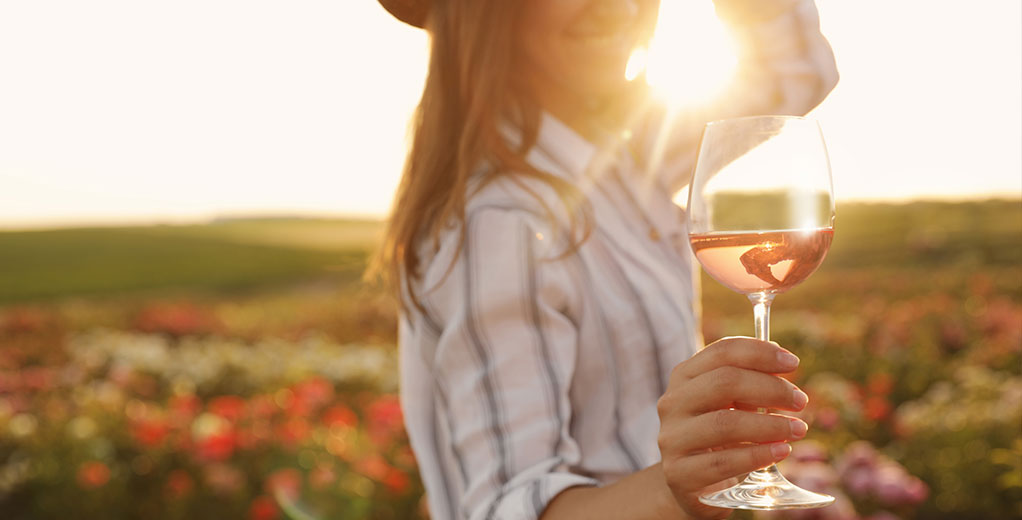 Frau in Wiese mit Weinglas